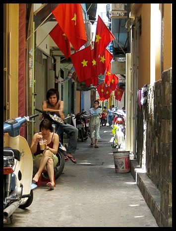 An alley riddled with flags of Vietnam.