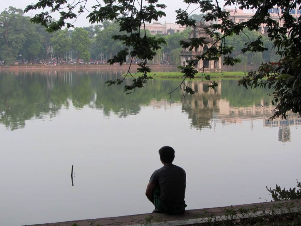 A man looking into the air at Hoan Kiem Lake, a popular meeting place in Hanoi
