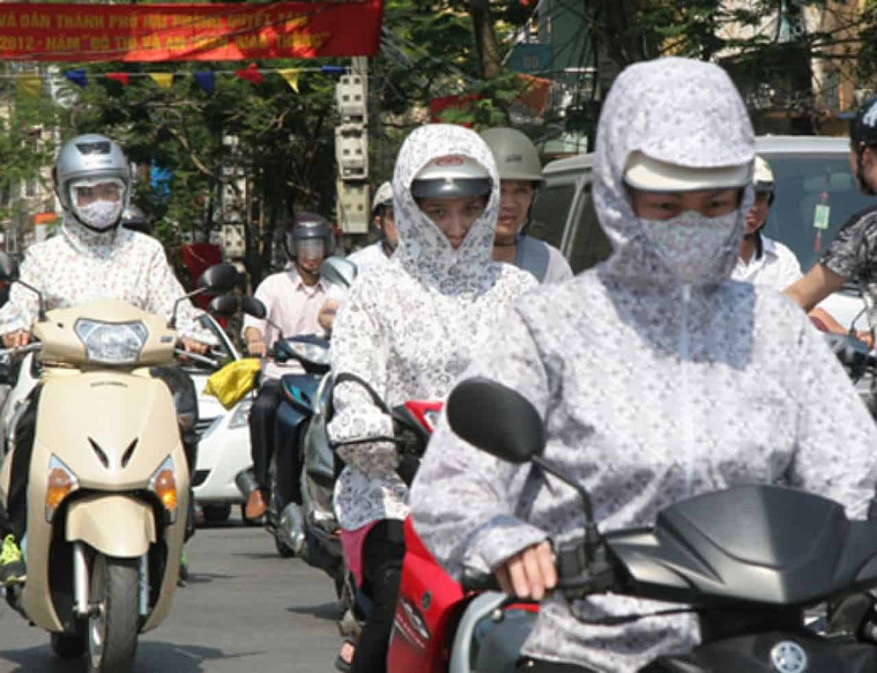 Vietnamese motorbike drivers shielded from the sun