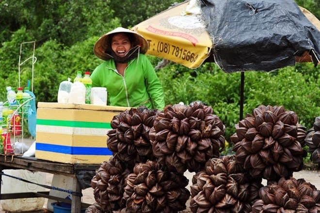 A smiling woman selling Dua Nuoc on the road from Can Gio to Sai Gon during a Ho Chi Minh City day trip