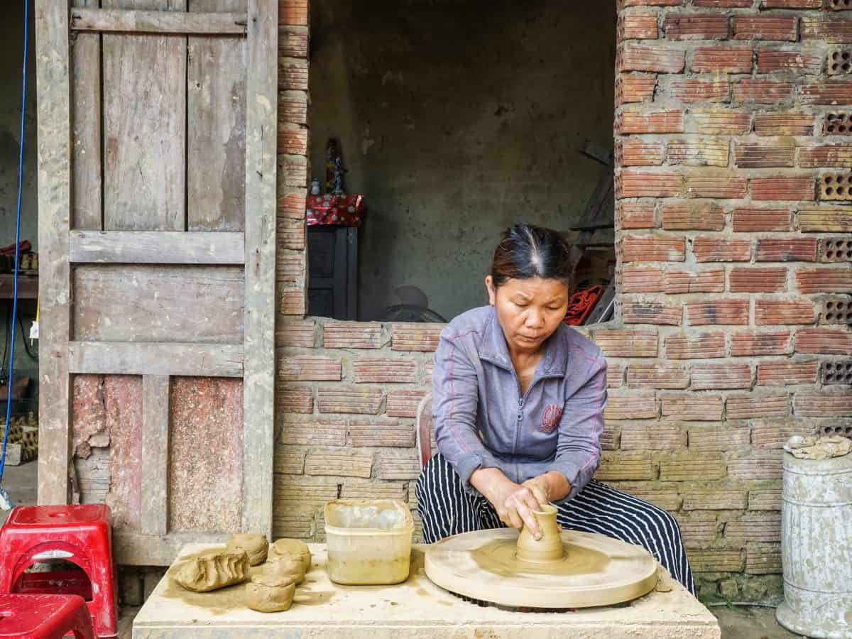 A female middle age worker is hand shaping pottery vase while sitting down at Ha Thanh pottery