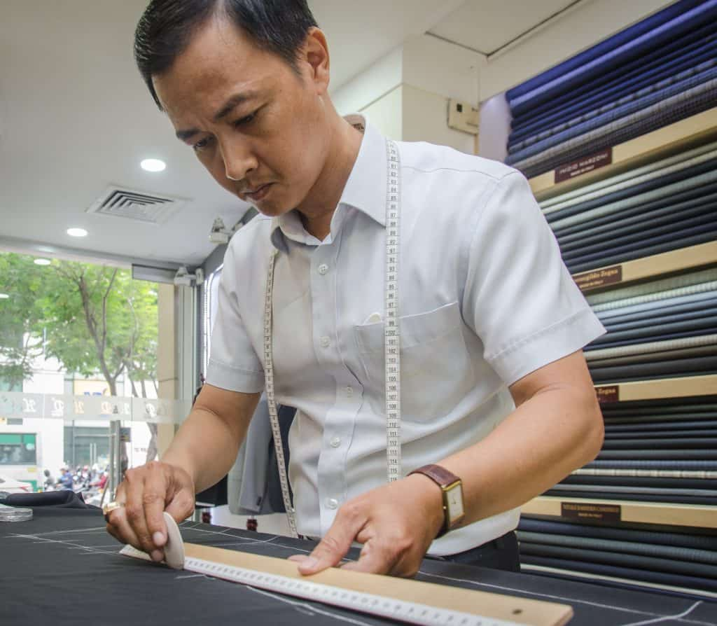 One of the best tailors in Hoi An measuring cloth