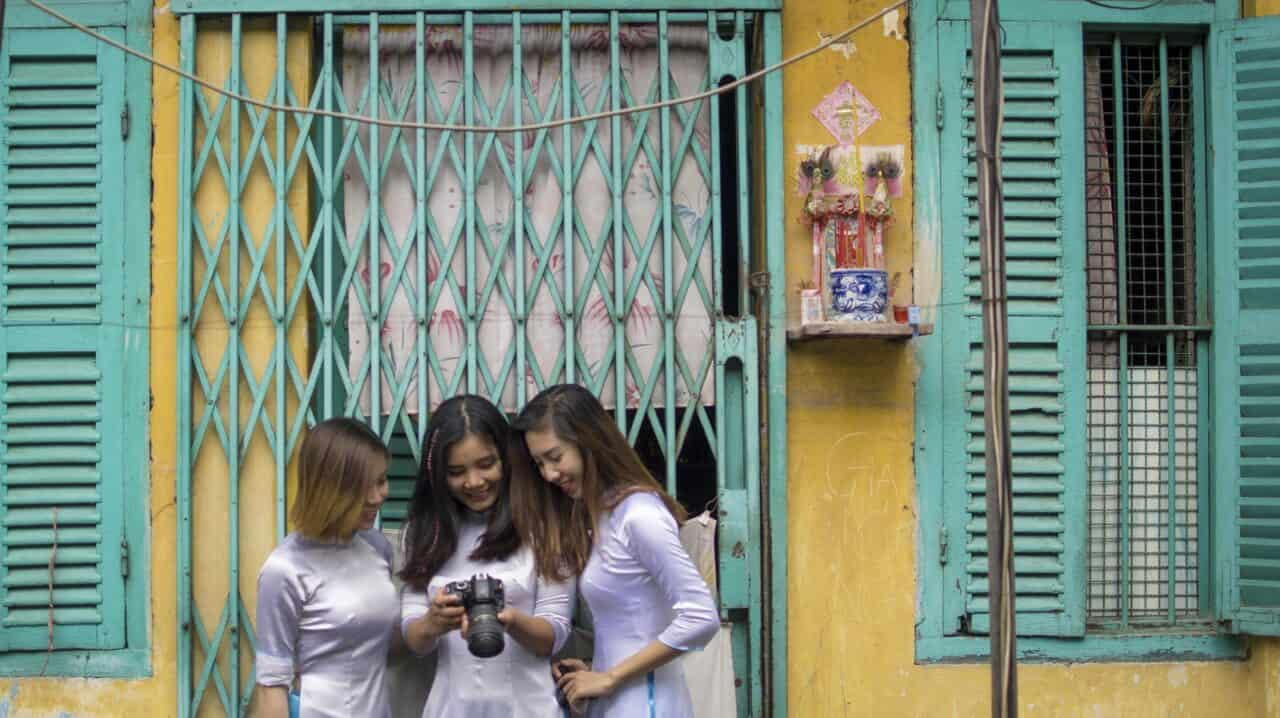 looking at a camera on Saigon Photography Tour